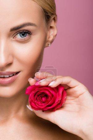 Photo pour Vue recadrée de belle femme blonde à la peau parfaite et fleur rose isolée sur rose - image libre de droit