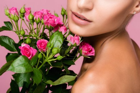 cropped view of beautiful woman with rose bouquet isolated on pink
