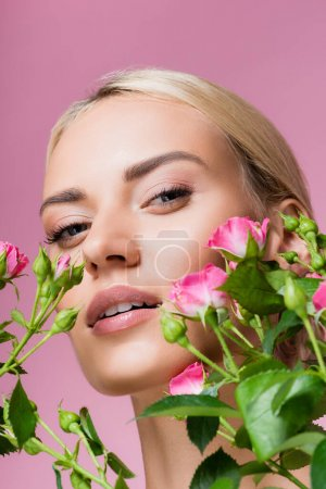 beautiful blonde woman in rose flowers isolated on pink