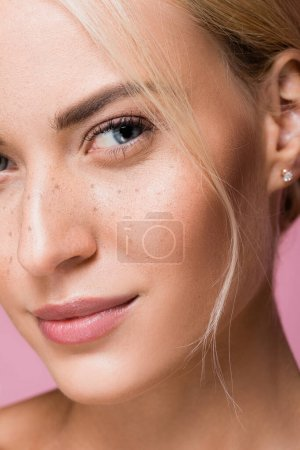closeup of beautiful woman with freckles isolated on pink