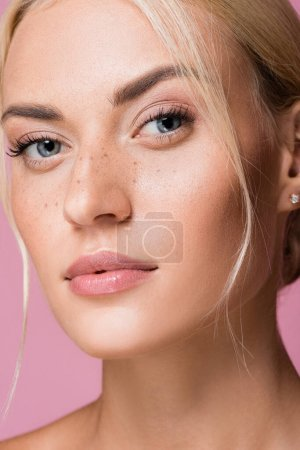 beautiful woman with freckles isolated on pink