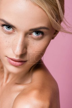 beautiful blonde woman with freckles and bare shoulders isolated on pink