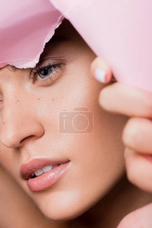 closeup of beautiful woman with freckles in pink paper hole