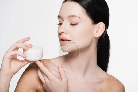 young beautiful woman with vitiligo holding cosmetic cream isolated on white