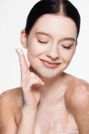 Photo pour Souriant jeune belle femme avec vitiligo appliquer crème cosmétique isolé sur blanc - image libre de droit