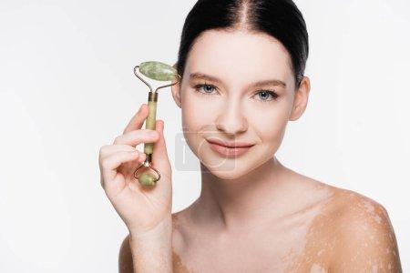 lächelnde junge schöne Frau mit Vitiligo hält Jade-Rolle im Gesicht isoliert auf weiß