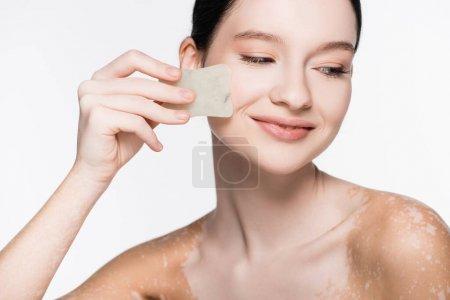 Photo pour Sourire jeune belle femme avec vitiligo en utilisant gua sha isolé sur blanc - image libre de droit