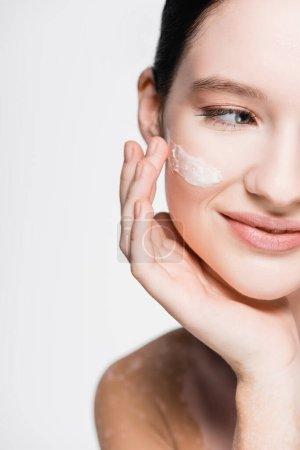 Photo pour Vue recadrée de belle femme souriante avec vitiligo et crème faciale sur la joue isolée sur blanc - image libre de droit