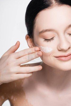 abgeschnittene Ansicht der jungen schönen Frau mit Vitiligo und Gesichtscreme auf der Wange isoliert auf weiß