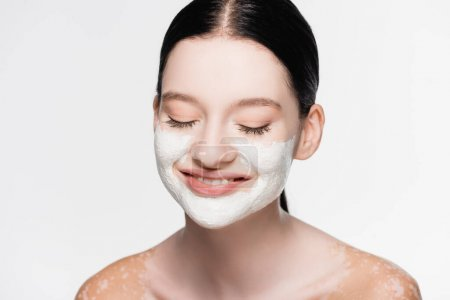 smiling young beautiful woman with vitiligo and clay mask on face isolated on white