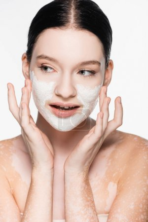 young beautiful woman with vitiligo and clay mask on face isolated on white