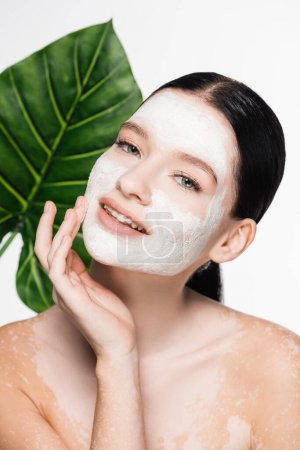 young beautiful woman with vitiligo and clay mask on face with blurred leaf on background isolated on white