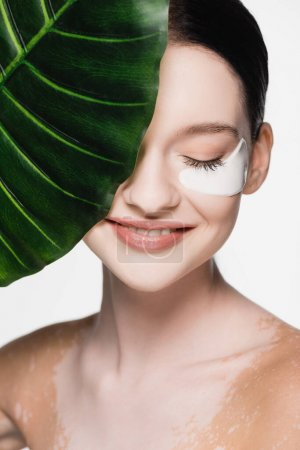 smiling young beautiful woman with vitiligo and eye patches on face near green leaf isolated on white