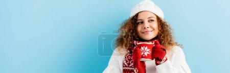 Photo for Cheerful and curly woman in hat and sweater holding cup of tea in knitted holder on blue, banner - Royalty Free Image