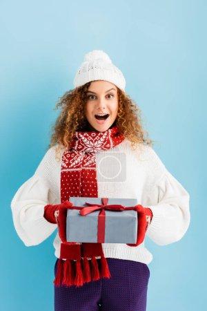 Photo pour Femme excitée dans le chapeau et les mitaines tenant boîte cadeau enveloppé sur bleu - image libre de droit