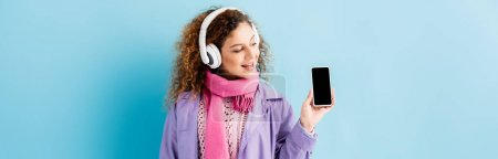 glückliche junge Frau in kabellosen Kopfhörern, Wintermantel und rosa Schal mit Blick auf Smartphone mit leerem Bildschirm auf blauem Hintergrund, Banner