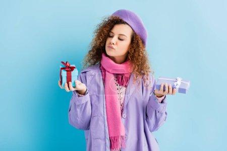 Photo pour Femme bouclée en manteau d'hiver, béret et écharpe tricotée rose au choix entre les cadeaux de Noël sur bleu - image libre de droit