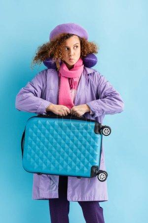 młoda kręcone kobieta w płaszcz i szalik gospodarstwa walizka na niebiesko