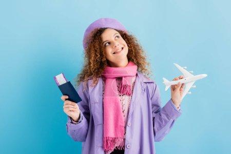 Lächelnde Frau in Baskenmütze, Schal und Mantel mit Pass und Spielzeugflugzeug auf blau