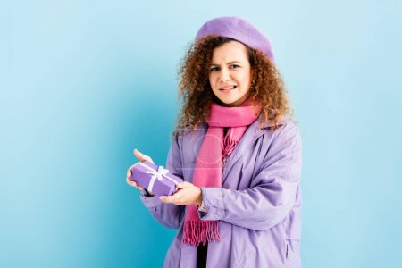 confused woman in winter coat, beret and pink knitted scarf holding christmas present on blue