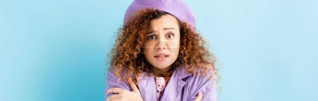 Photo for Curly woman in beret freezing and embracing herself on blue background, banner - Royalty Free Image