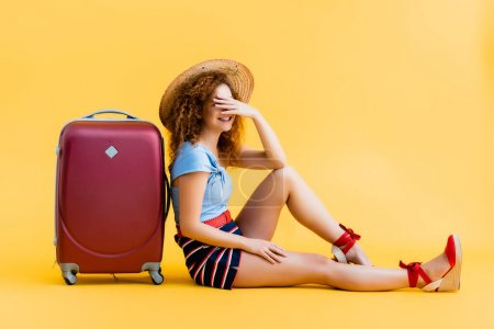 cheerful and curly woman covering face while laughing and sitting near suitcase on yellow