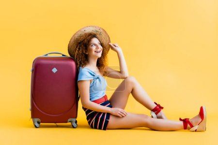 cheerful and curly woman adjusting straw hat while laughing and sitting near suitcase on yellow