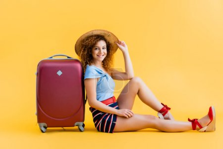 happy and curly woman adjusting straw hat while sitting near suitcase on yellow