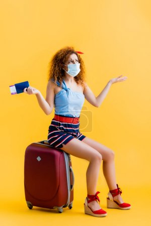 Photo for Confused young woman in medical mask holding passport while sitting on suitcase on yellow - Royalty Free Image