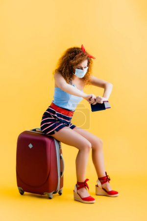 curly young woman in medical mask tearing passport while sitting on suitcase on yellow