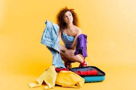 Photo pour Femme confus assis près de la valise et tenant des vêtements sur jaune - image libre de droit