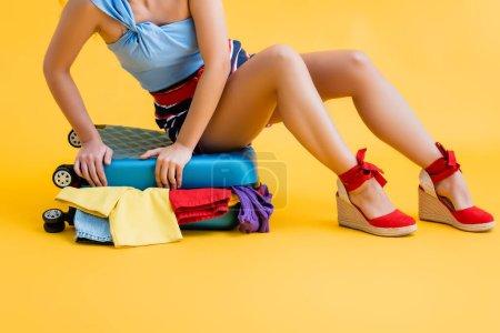 Photo pour Vue partielle de la jeune femme assise sur une valise avec des vêtements jaunes - image libre de droit