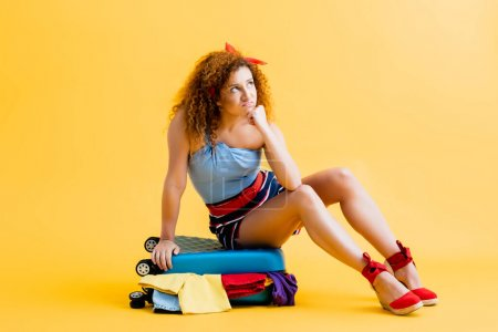 Photo for Displeased young woman sitting on suitcase with clothing on yellow - Royalty Free Image