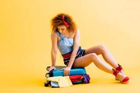 Photo for Curly young woman sitting on luggage with clothing on yellow - Royalty Free Image