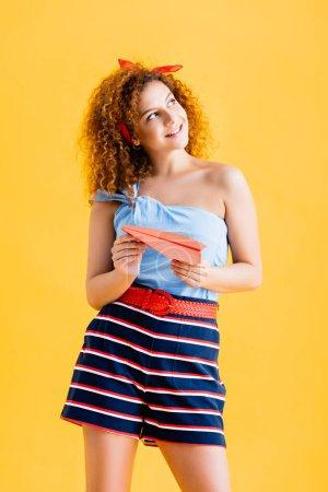 alegre joven en traje de verano sosteniendo avión de papel en amarillo