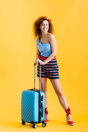 Photo for Full length of positive woman in summer outfit and wedge sandals standing near suitcase on yellow - Royalty Free Image