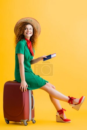 full length of cheerful woman in straw hat holding passport and sitting on red luggage on yellow