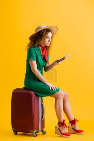 Photo for Full length of angry woman in straw hat holding passport and sitting on luggage on yellow - Royalty Free Image