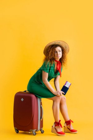 full length of upset woman in straw hat holding passport and sitting on red luggage on yellow