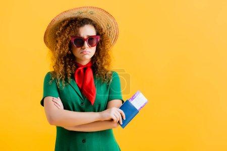 Frustrierte Frau mit Strohhut, Sonnenbrille und Kleid mit gelbem Pass