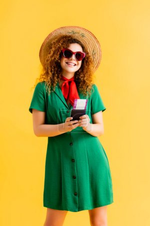 Photo for Happy woman in straw hat, sunglasses and dress holding passport on yellow - Royalty Free Image