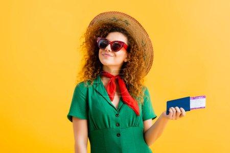 mujer alegre en sombrero de paja, gafas de sol y vestido con pasaporte en amarillo