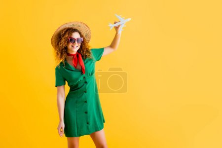 cheerful woman in straw hat, sunglasses and dress holding toy plane on yellow