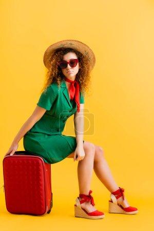 longitud completa de la mujer triste en sombrero de paja, gafas de sol y vestido sentado en el equipaje en amarillo