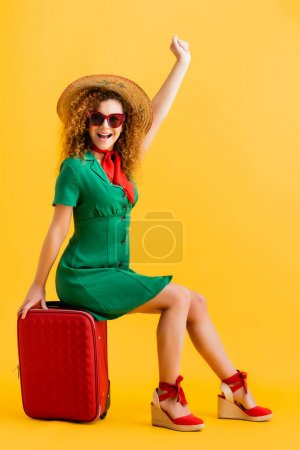 Photo for Full length of excited woman in straw hat, sunglasses and dress sitting on luggage on yellow - Royalty Free Image