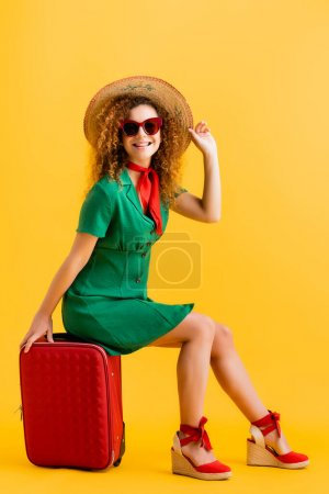 full length of cheerful woman in straw hat, sunglasses and dress sitting on luggage on yellow
