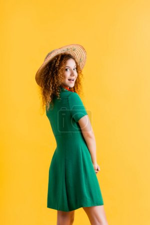 cheerful young woman in straw hat and green dress isolated on yellow