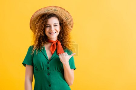 Photo for Happy young woman in straw hat and green dress pointing with thumb isolated on yellow - Royalty Free Image