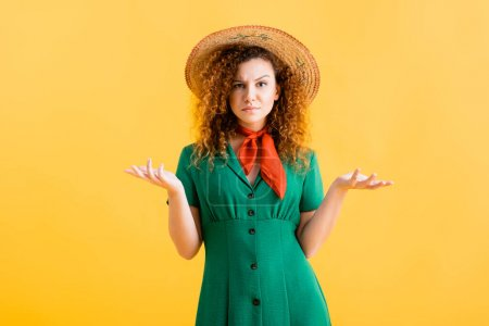 Photo for Confused young woman in straw hat and green dress gesturing on yellow - Royalty Free Image