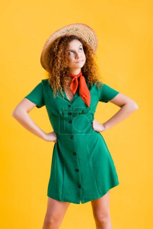 displeased woman in straw hat and green dress standing with hands on hips on yellow